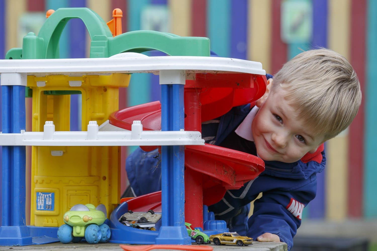 Nursery child playing with toy garage
